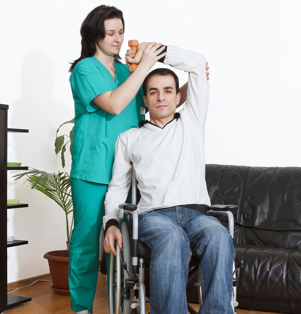 Man in wheelchair having phisiotherapy with a nurse at home